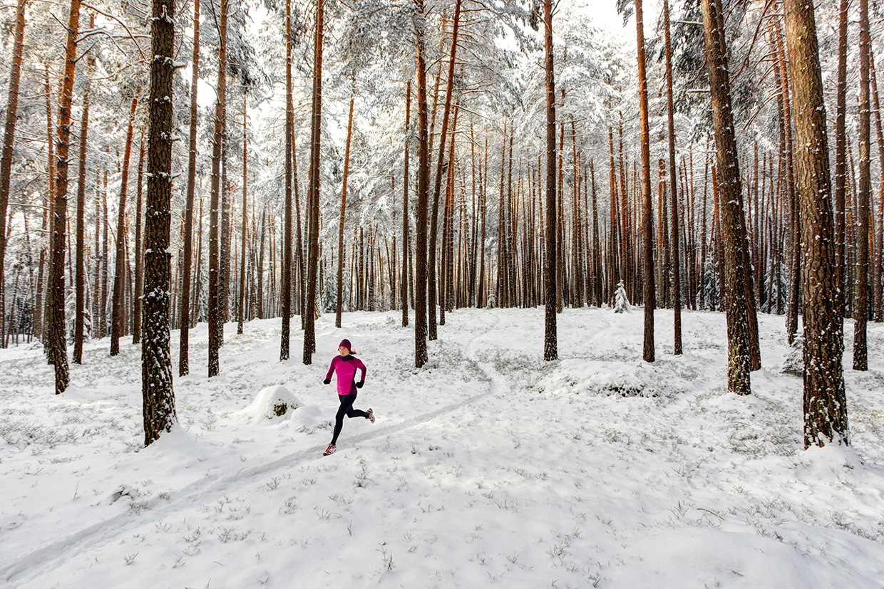 Woman winter trail running in forest