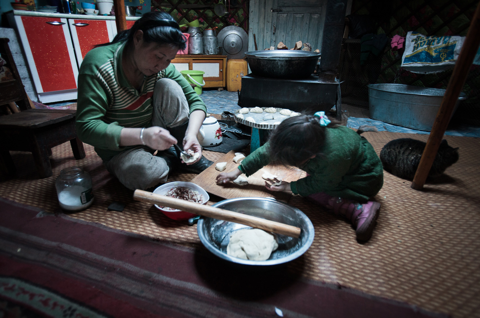 Mother and daughter prepare buuz, a Mongolian steamed dumpling filled with meat.