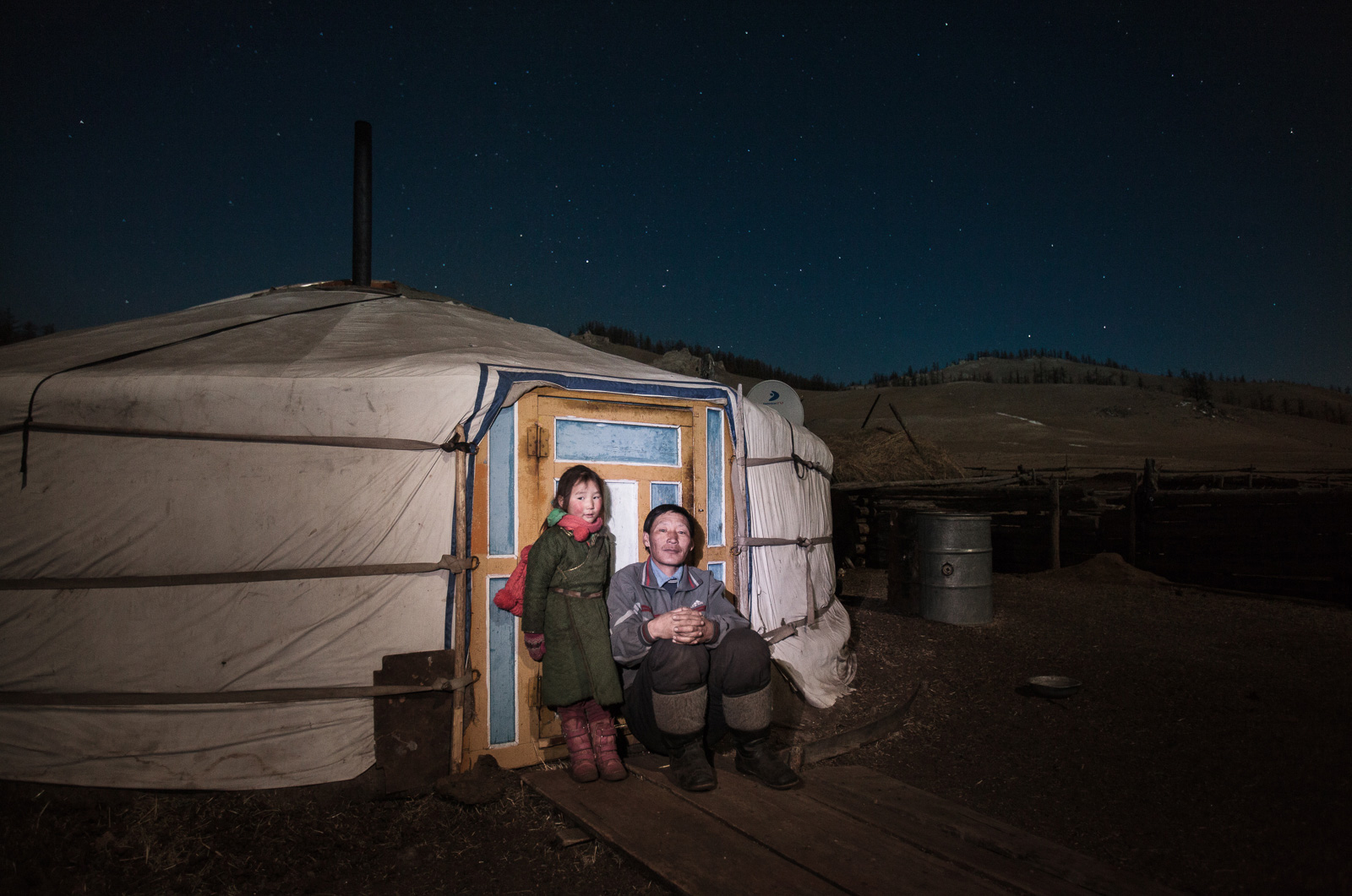 Father and daughter posing for a cold night portrait at their ger's doorstep. Although life in the steppe is rude, there is a great complicity between the members of the family and a lot of humour.